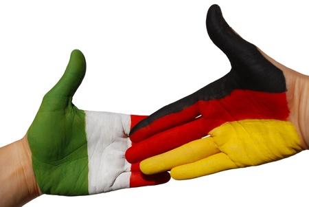 tratados: un apret�n de manos entre dos manos que se pintan con el alem�n y la bandera italiana Foto de archivo