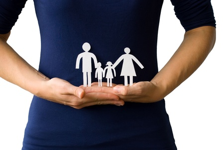 family life: hands holding a paper chain family in front of a body, on white Stock Photo