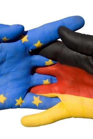 tratados: dos manos en un apret�n de manos, una mano pintada con el alem�n y el otro con los colores europeos Foto de archivo