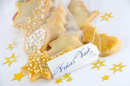 weihnachten: some christmas cookies with a marker tag on which stands handwritten Frohe Weihnachten