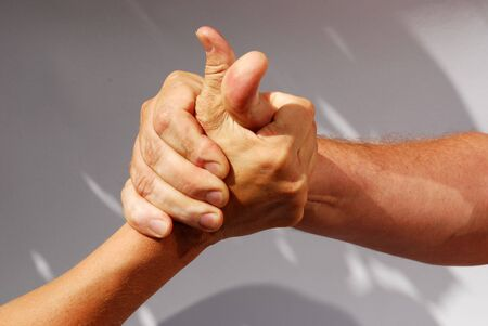 parship: two middle aged hands competing or handshaking Stock Photo