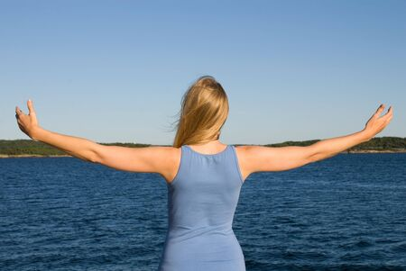 arms wide open: a young woman with arms wide open at the sea