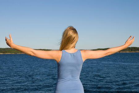arms wide: una giovane donna con le braccia spalancate al mare