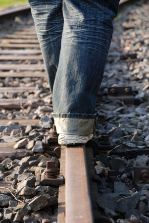 a person balancing on a railway track, danger photo