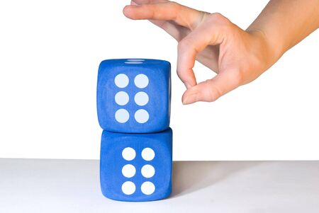 overbalance: hand overbalancing two blue dice with a six on each