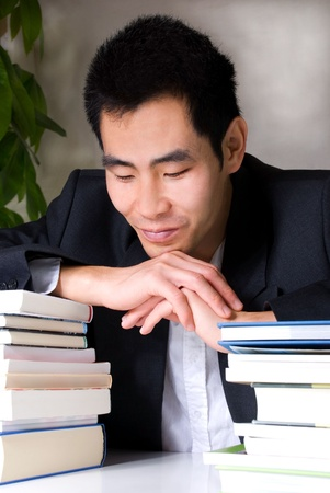 asian looking man lying with his arms on many book; looking tired photo