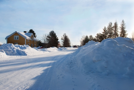 artic circle: a street full of snow with some houses, snow landscape Stock Photo