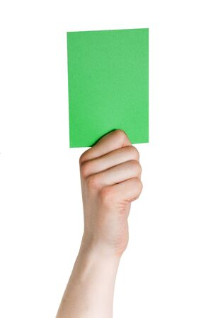 a hand holding a green tag, voting or electing, isolated photo