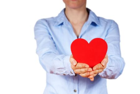 a person with blue shirt holding a heart in its hands, isolated photo