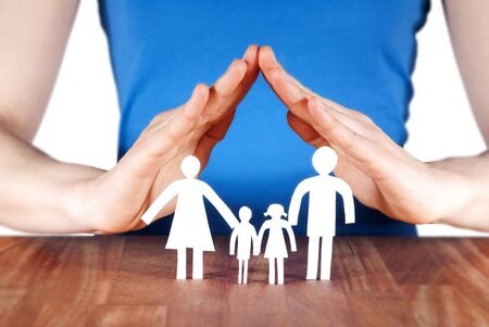 homelike: a family standing under a roof of a house build of hands Stock Photo