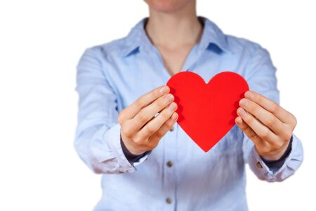 a person with blue shirt holding a heart in its hands photo