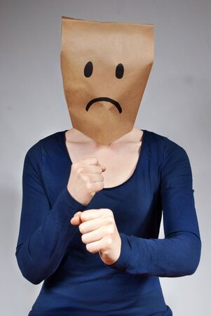 masquerading: a woman with a a sad paper bag head defending herself Stock Photo