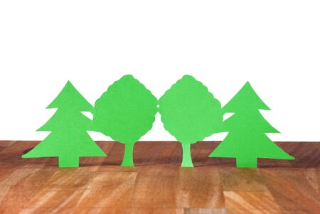 environmental conversation: some trees symbolizing wood and forest on a wooden plank, isolated