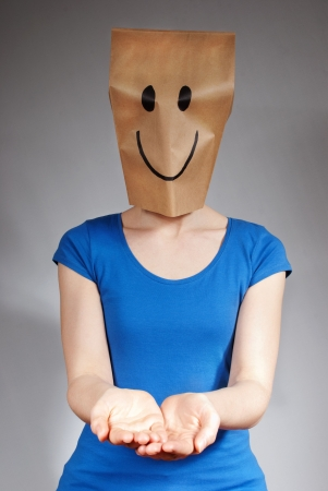 masquerading: a happy person holding up its hands with copy space, gray background