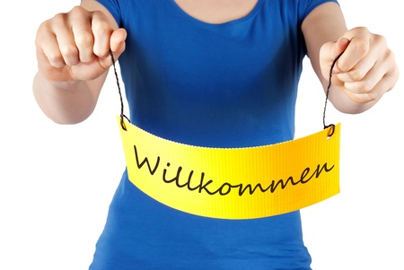 willkommen: a woman holds a yellow banner with Willkommen on it, which is the german word for welcome, isolated Stock Photo