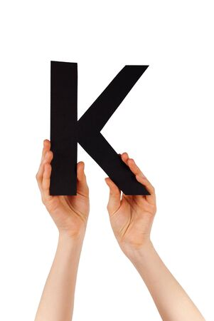 illiterate: the letter K, hold by hands, isolated Stock Photo
