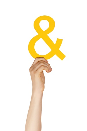 hand holding a yellow ampersand symbolizing and, isolated photo