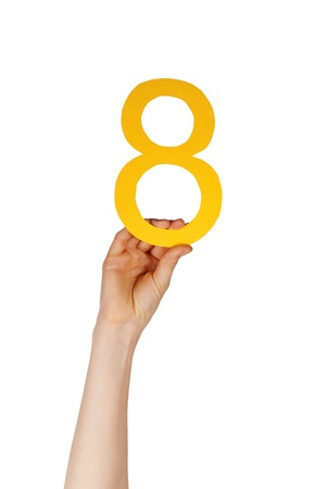 a hand holding up a yellow number eight, isolated Stock Photo - 19745619