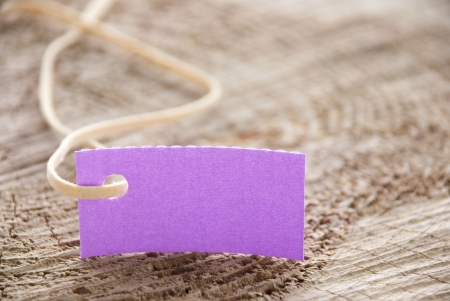 attachement: a purple label tag with copy space on a trunk of wood Stock Photo