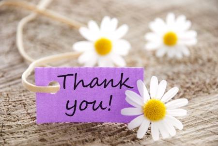 een paarse label met Dank u op en bloemen op de achtergrond Stockfoto