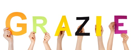 many hands holding the italian word grazie which means thanks, isolated Stock Photo
