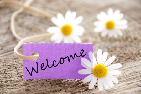 welcome sign: a purple banner with welcome on it and flowers in the background