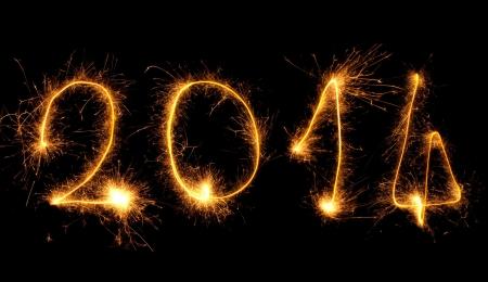 turns of the year: 2014 escritos con los fuegos artificiales, que simboliza Nochevieja Foto de archivo
