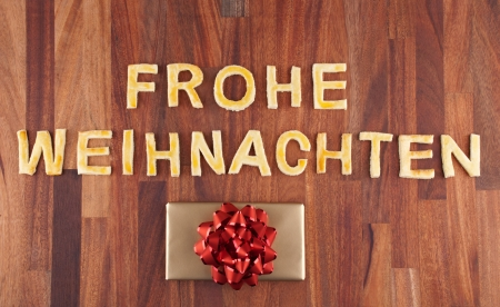 the german word Frohe Weihnachten which means merry christmas with a gift photo