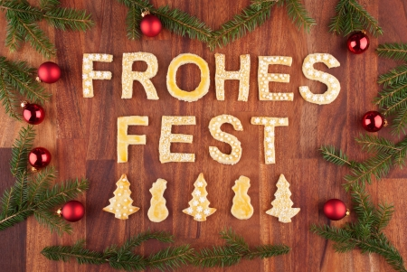 the german words frohes fest which means merry christmas with christmas decorations and cookies photo