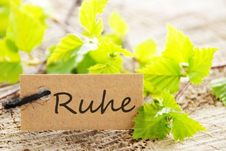a natural looking label with green leaves and wood as background, with the german word Ruhe on it which means calmness Stock Photo