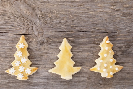 three different decorated christmas tree cookies on a wooden background with copy space photo