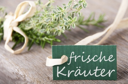 a green label with the german words frische Kr�uter which means fresh herbs, herb background photo