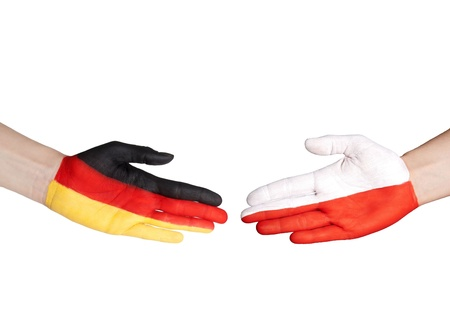 two hands with german and polish flag doing a handshake photo