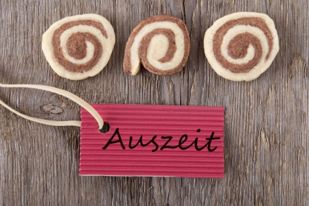 auszeit: a red label with the german word Auszeit which means downtime and some cookies on a wooden background Stock Photo