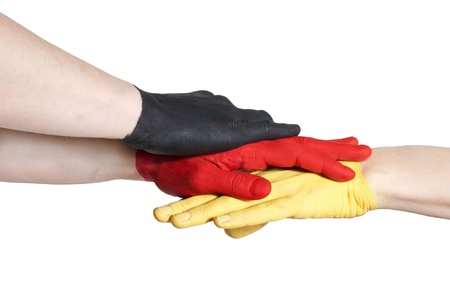 a black, a red and a yellow painted hand building a team symbolizing handshake
