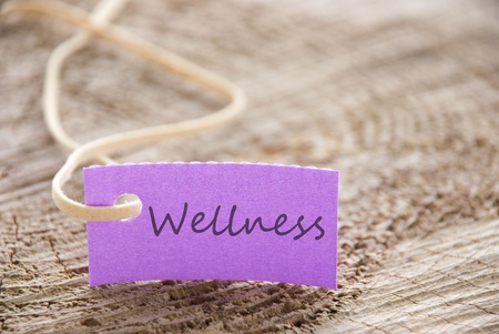 healthfulness: a purple label with wellness on it as background Stock Photo