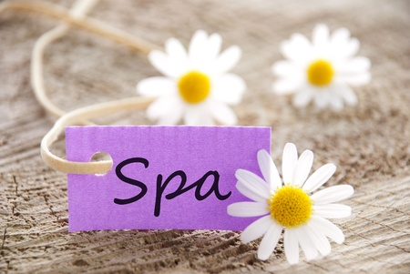 a purple label with the word spa on it and with white blossoms in the background photo