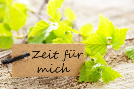 a natural looking label with green leaves and the german words Zeit fuer mich which means time for myself and wood as background Stock Photo