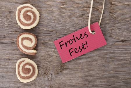 the german words Frohes Fest which means merry christmas on a red banner with cookies photo
