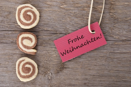 the german words Frohe Weihnachten which means merry christmas on a red label with cookies as background photo