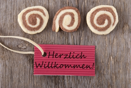 willkommen: the german words Herzlich Willkommen which means welcome on a red label with cookies on wooden background