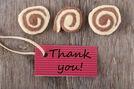 a red label with thank you on it with cookies on a wooden background