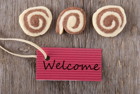 a red label with welcome on it and some cookies on a wooden background Stock Photo - 20465354