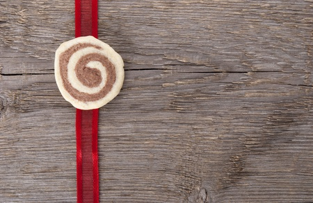red ribbon with a cookie on wood with copy space as background photo