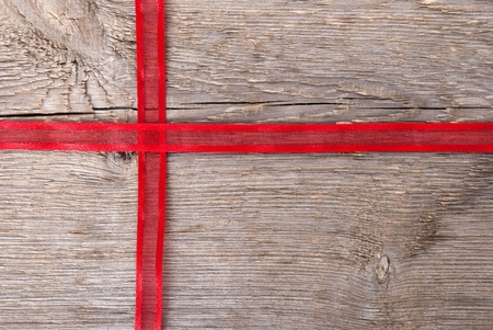 red ribbon on wood in shape of a cross with copy space as background photo