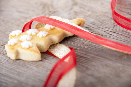 a christmas tree cookie in red and golden ribbon as christmas background photo