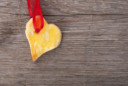 a baked heart with copy space hanging on red ribbon on wooden background photo