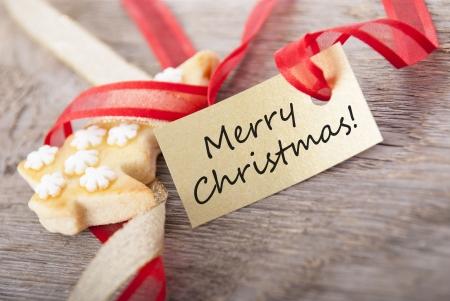 galletas de navidad: un fondo de Navidad con una etiqueta dorada en la que se encuentra feliz navidad Foto de archivo