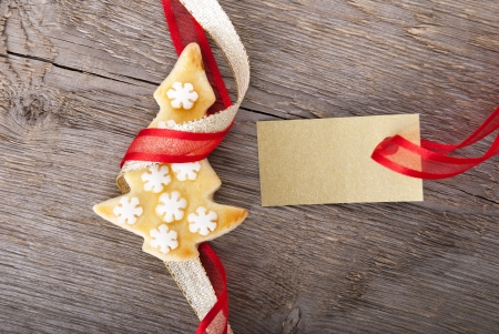 a golden tag with copy space and a christmas cookie as christmas background photo