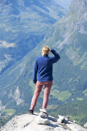 A Woman Looking or Searching efter Something on the Pike of a Mountain photo